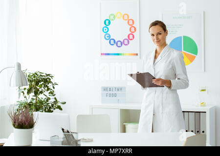 Professional nutritionist in white uniform in the office with plant and colorful posters - Stock Photo