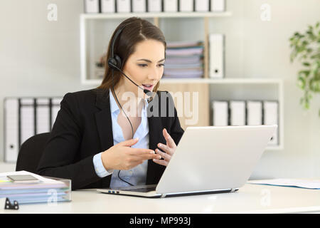 Telemarketer talking on-line having a video call with a laptop at office - Stock Photo