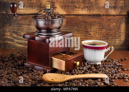 Coffee mill grinder and cup of coffee and wooden spoon on old retro background with roasted beans. Retro and vintage drink concept - Stock Photo