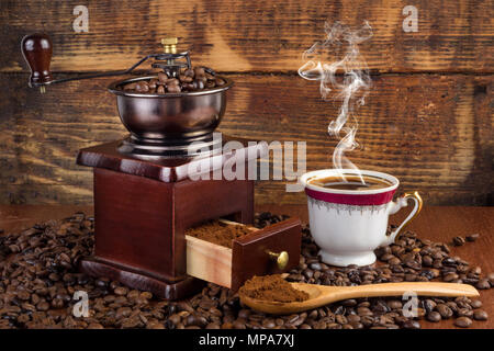 Coffee mill grinder and cup of coffee with smoke and wooden spoon on retro background. Retro and vintage drink concept - Stock Photo