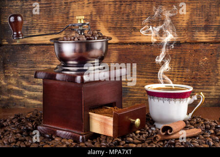 Retro coffee mill and  cup with black coffee smoking on wooden background. Retro and vintage drink concept - Stock Photo