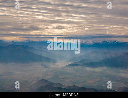 View from plane window flying South from Santiago, Chile with Andes mountain peaks and cloud layers broken by shafts of light falling on valley - Stock Photo