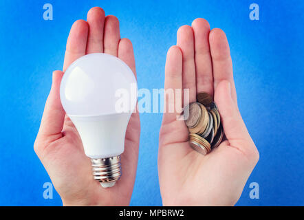 LED lamp and a pile of coins in hands, palms on a blue background. The concept of energy conservation - Stock Photo