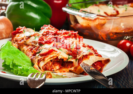 Traditional mexican enchiladas with chicken meat, spicy tomato sauce and cheese on a plate. Mexican cuisine. - Stock Photo
