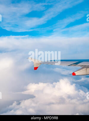 British Airways Airbus 319 plane wing seen from plane window during flight above puffy and wispy clouds and clear blue sky in United Kingdom - Stock Photo
