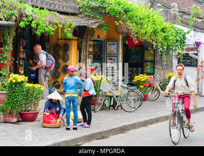 Hoi An, Vietnam - February 17, 2016: Man on bicycle at the street of old city of Hoi An, Vietnam - Stock Photo