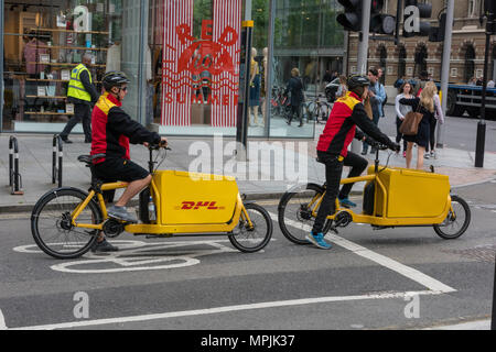 two DHL global logistics delivery drivers riding cycles to deliver parcels and courier services in the centre of london. DHL global international post - Stock Photo