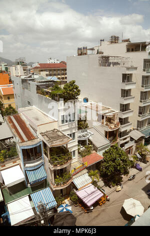 Asian town buildings and a road cityscape top view. Tranquil sunny Vietnamese city view from above - Stock Photo