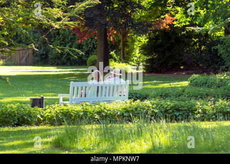Beautiful happy couple sitting in the park on a bench - Stock Photo