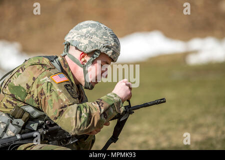 U.S. Army Spc. Mitchell Cooper adjusts his M4's front sights before shooting a weapon qualification during the New York Army National Guard Best Warrior Competition at Camp Smith Training Site March 30, 2017. The Best Warrior competitors represent each of New York's brigades after winning competitions at the company, battalion, and brigade levels.  (U.S. Army National Guard photo by Sgt. Harley Jelis) - Stock Photo