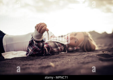 cute young woman rest on the beach with sand falling from her hand. freedom and wanderlust concept on vacation - Stock Photo