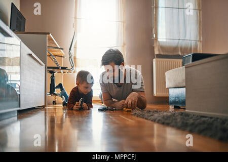 Father and son lying together on the floor playing with toy cars - Stock Photo