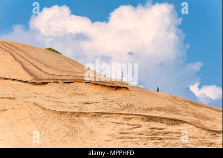 At Pacific City, Oregon, a hill of sand is a favorite activity to hike up to the top.  Big fluffy white clouds hoover over a couple hiking towards the - Stock Photo