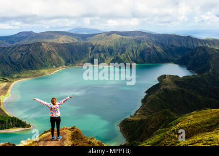 Azores, Sao Miguel, Woman with raised arms on the top of the Lagoa do Fogo - Stock Photo