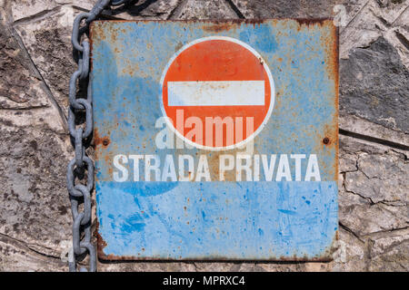 Rusty italian no entry signpost with private road indication fixed on a stone wall and a chain - Stock Photo