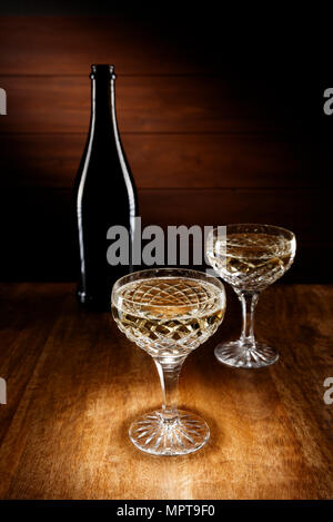 Spotlight on two Champagne crystal glasses with a bottle in background, shot on a antique wooden table top. - Stock Photo