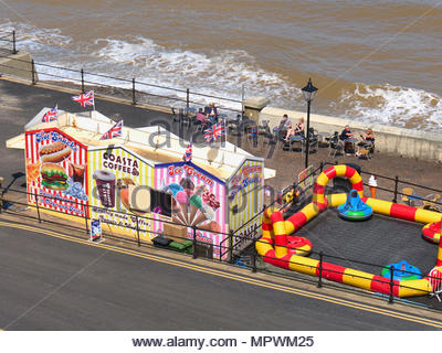 Looking down onto a childrens play area with snacks coffee ice cream stalls on Cromer seaside resort in Norfolk UK - Stock Photo
