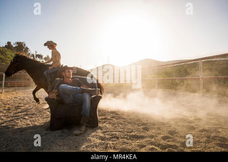 couple of beautiful man and woman together. she rides a horse making dust with speed and he stays sit down on the chair in the middle of the track - Stock Photo