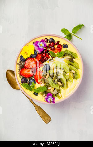 Mango banana pineapple turmeric breakfast superfoods smoothie bowl topped with fruits, berries and seeds. Overhead top view flat lay - Stock Photo