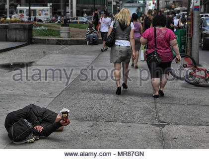 Pedestrians walk past a homeless man laying the sidewalk and holding a cup begging for spare change in downtown Toronto, Canada. Homelessness is a big - Stock Photo