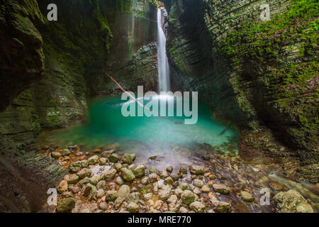 Hidden Kozjak waterfall streams out of layered, mossy rocks in a deep gorge.Blue water, insane crystal clear pool, rocks and dead tree. Long exposure. - Stock Photo