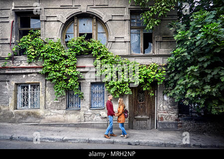 Happy couple of tourist near vintage house with round window at old streets of central Tbilisi, Georgia - Stock Photo