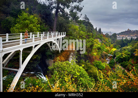 Tourist Woman in Hat at white bridge in Botanical Garden with autumn trees at overcast cloudy sky in Tbilisi, Georgia - Stock Photo