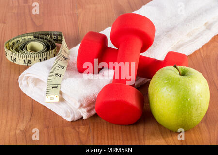 Red fitness dumbbell, measuring tape and green fresh apple with dew on white towel and wooden floor. Diet, sport and health food concept - Stock Photo