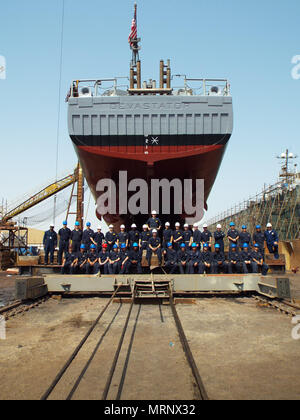 170617-N-XP344-001 MANAMA, Bahrain (June 17, 2017) – The crew of USS Devastator (MCM 6) stands underneath the ship's hull before it leaves dry dock. Devastator upgraded in several warfare areas, including mine warfare, cyber readiness, and engineering as well as improvements to the engineering plant, underwater hull, crew living spaces, and the installation of the AN/SLQ-60 SeaFox mine neutralization system.  (U.S. Navy photo) - Stock Photo