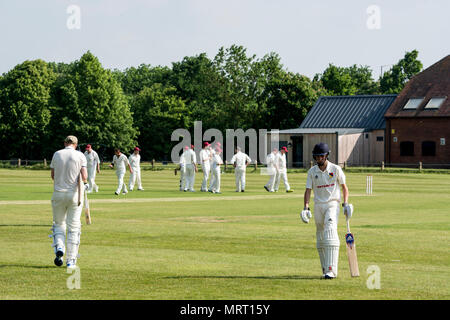 Village cricket at Wellesbourne, Warwickshire, England, UK. Batsmen changing places after one is out. - Stock Photo