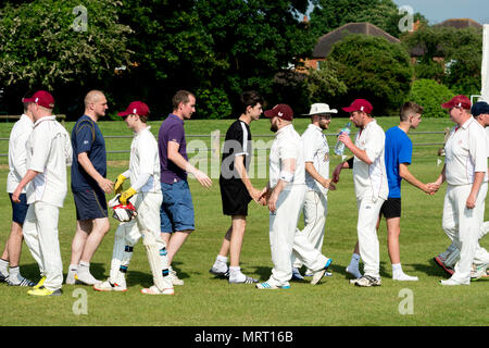 Village cricket at Wellesbourne, Warwickshire, England, UK. Players shaking hands after the match. - Stock Photo