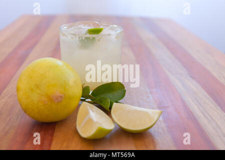 Key lime margarita garnished with fresh lime in a glass bar table - Stock Photo