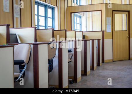 Small individual cabins with computers and chairs in an office - Stock Photo