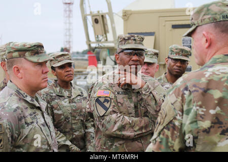 Brig. Gen. Douglas McBride, center, commanding general of the 13th Expeditionary Sustainment Command, listens as Maj. Gen. Joseph P. Harrington, far right, U.S. Army Africa commander, speaks with Soldiers from the 35th Signal Brigade on July 29, 2017, about the job they are doing during Exercise Judicious Activation 17-2 in Libreville, Gabon. Judicious Activation is a U.S. Africa Command exercise, executed by U.S. Army Africa this cycle, focused on increasing contingency response force capacity to support stability operations on the African continent. (Photo by Sgt. 1st Class Alexandra Hays, 7 - Stock Photo