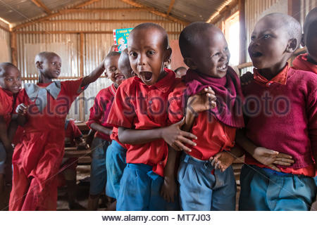 A group of school children at a Masai village in Kenya, playing laughing during recess in their old dirty school uniforms. - Stock Photo