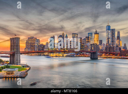 New York, New York, USA skyline of Manhattan over the East River with the Brooklyn Bridge after sunset. - Stock Photo
