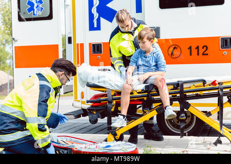 Emergency doctors caring for accident victim boy - Stock Photo