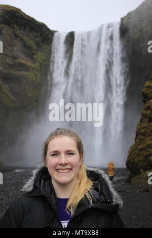Young female tourist aged 20 to 25, poses and smiles in front of a large waterfall in iceland named skogafoss waterfall. Iceland has become a trendy travel location - Stock Photo