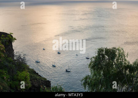 Cruising yachts on the well maintained mooring buoys off Jamestown at dusk, in the lee of the remote tropical island of St Helena, South Atlantic - Stock Photo