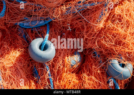 Fishing net with blue rope and buoys on the dock. Close up. - Stock Photo