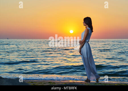 Beatiful girl walking alone on sandy beach on colorful sunset. Looking on amazing deep blue sea and waves. Breezing fresh sea breeze. Watching on sun going down the horizon. Wearing long white dress. - Stock Photo