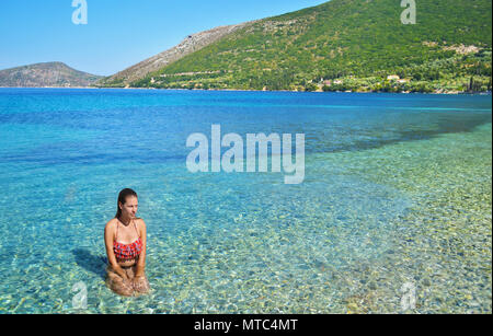 greek girl sitting inside the sea at Ithaca Ionian islands Greece - Stock Photo