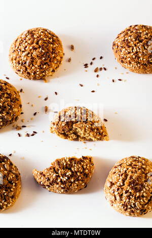 freshly baked oatmeal cookies sprinkled with sunflower seeds, linseed and sesame seeds. healthy pastries on a white background - Stock Photo