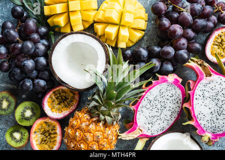 Assortment of exotic tropical fruits. Passionfruit, dragonfruit, mango, pineapple, kiwi, grapes and coconut. Fresh food background. Healthy eating, ve - Stock Photo