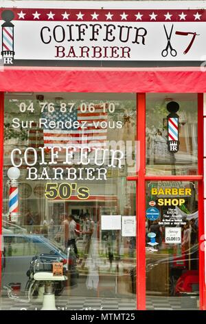 Barber shop with an American, usa, decor and an old sign. Renewal of barbers in France thanks to a clientele of hipsters. Grenoble, Isere - Stock Photo