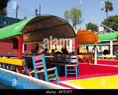 XOCHIMILCO, MEXICO on MARCH 2018: Colourful Mexican boats with tourists at Floating Gardens in warm sunny winter day. - Stock Photo