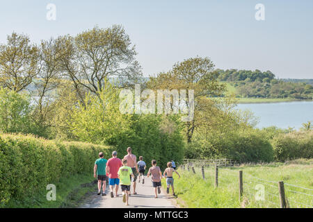 A group of three men walk down a road on a hot day to Rutland Water lake, England, as four children run past them. - Stock Photo