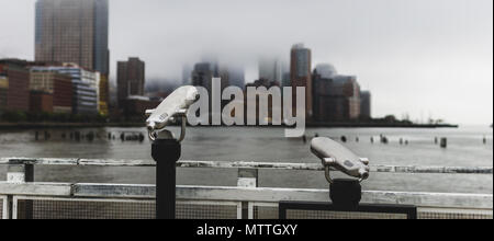 Two viewfinders overlooking lower Manhattan as it is covered in fog. - Stock Photo