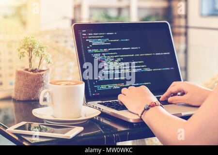 A programmer typing source codes in a coffee shop. Studying, Working, Technology, Freelance Work, Web Design Business, and Web Development Concept. - Stock Photo