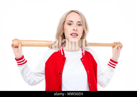Three quarter length shot of a young woman holding a baseball bat behind her shoulders. - Stock Photo